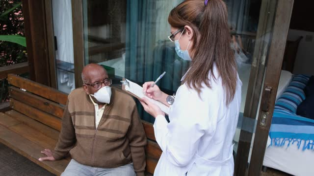 Doctor doing a questionnaire to patient at home - wearing face mask video