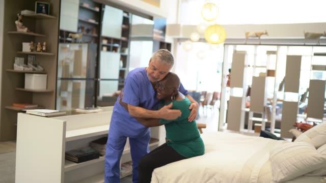 vidéos et rushes de docteur embrassant le patient - infirmier