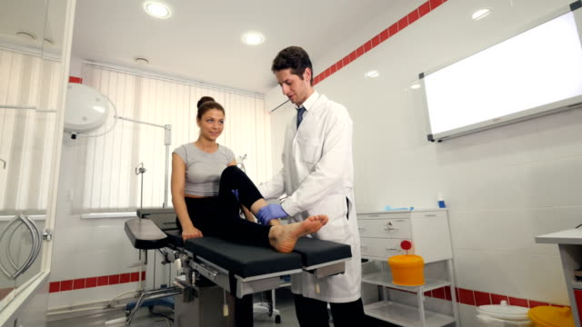 A doctor examines the girl's ankle at a hospital A girl with a broken ankle comes to see the doctor and get a treatment at a clinic ankle stock videos & royalty-free footage
