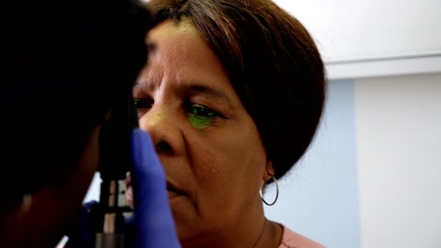 Doctor examines the patients eye An African female doctor examines the eye of a female patient eye exam stock videos & royalty-free footage