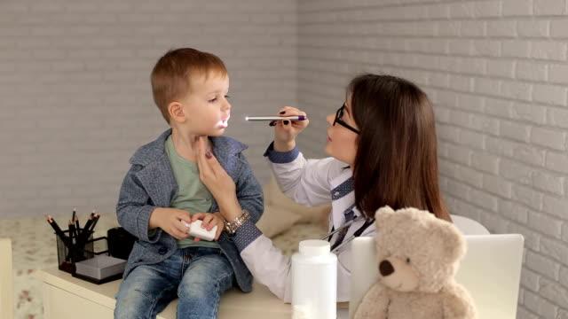 doctor examines the throat of boy with flashlight. - szpatułka przybór do gotowania filmów i materiałów b-roll