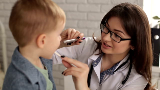 Doctor examines throat and mouth to a small child. video