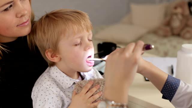 doctor examines throat and mouth to a small child. - szpatułka przybór do gotowania filmów i materiałów b-roll