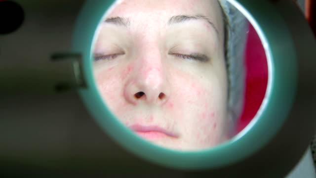 Doctor examinando la cara de un paciente - vídeo