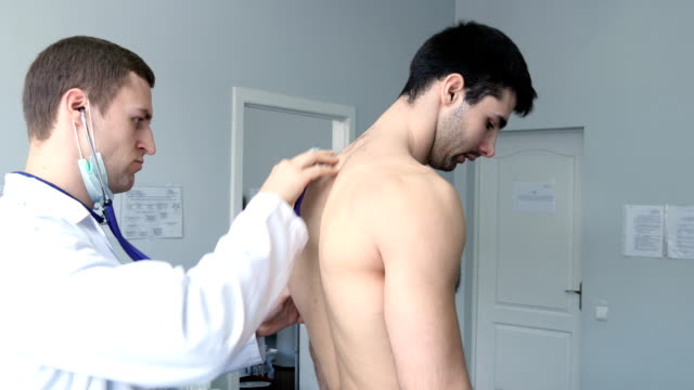 Doctor examining back of young male patient with stethoscope video