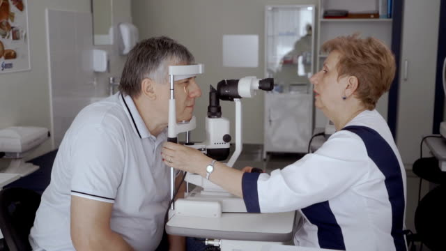 vidéos et rushes de médecin examinant la vue d'un homme adulte avec un équipement moderne - réfracteur