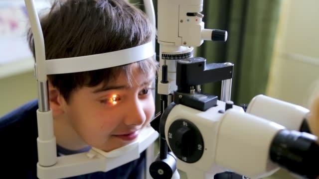 Doctor examining eyesight of cute kid, eye examination at slit lamp in oculist office Doctor examining eyesight of cute kid, eye examination at slit lamp in oculist office eye exam stock videos & royalty-free footage