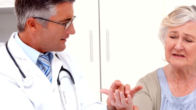 Doctor examining hand of patient video