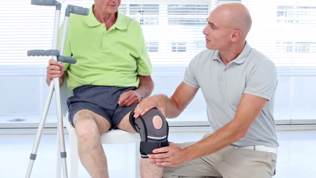 Doctor examining his patients knee Doctor examining his patients knee in medical office orthopedic equipment stock videos & royalty-free footage