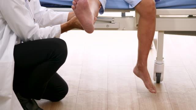 vídeos y material grabado en eventos de stock de médico examinando la pierna del paciente en la clínica - quiropráctico