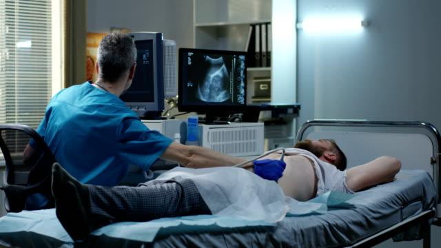 arzt untersucht mann mit ultraschall - bauch stock-videos und b-roll-filmmaterial