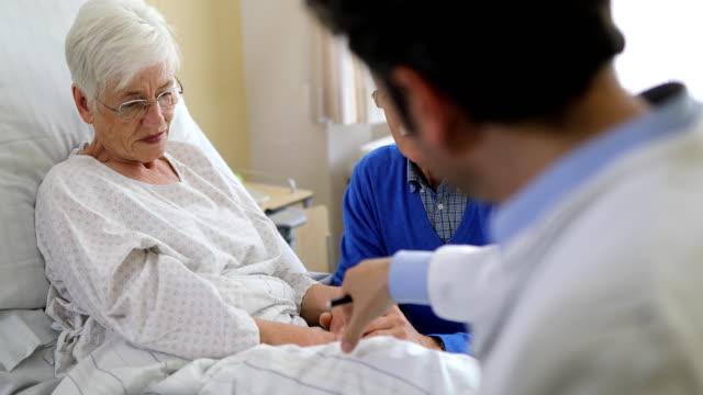 Doctor examining senior patient in hospital room