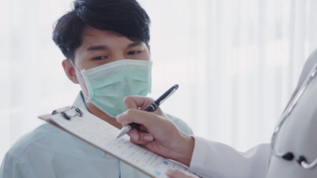 Doctor examining to patient Asian female Doctor examining and fill out a form to Asian Male patient in hospital flu shot stock videos & royalty-free footage