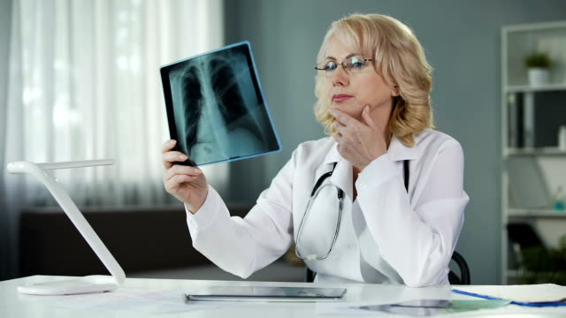 Doctor examining X-ray of patient's lungs making notes in medical records video