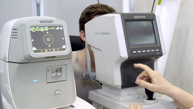 Doctor excaminating man's vision using machine video
