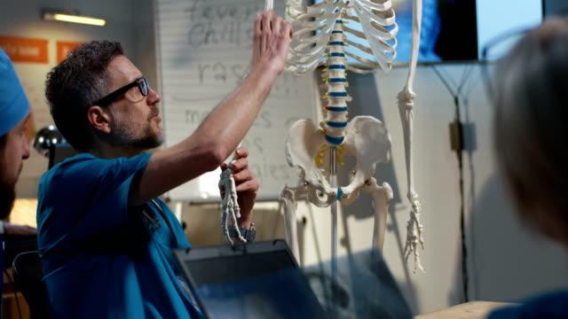 vídeos de stock, filmes e b-roll de doutor que explica o diagnóstico a seus colegas - ortopedia