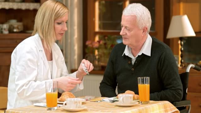 stockvideo's en b-roll-footage met dokter de pil gebruik protocol uit te leggen aan senior man - doordrukstrip