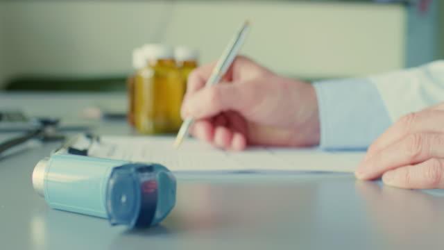 Doctor Filling Form On Clipboard By Inhaler On Desk 4K video