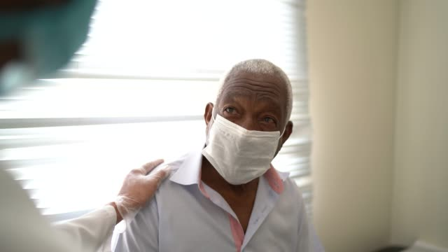 medico che dà supporto emotivo a un paziente anziano usando la maschera facciale - clinica medica video stock e b–roll