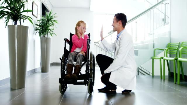 vídeos de stock e filmes b-roll de doctor giving high five to disable girl - capacidades diferentes