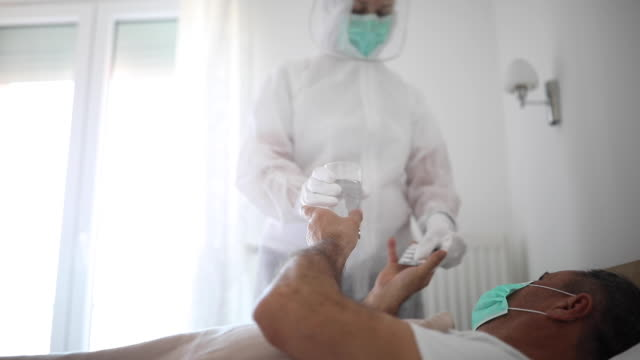 Doctor giving medicine to a senior man lying in hospital bed because of coronavirus infection video
