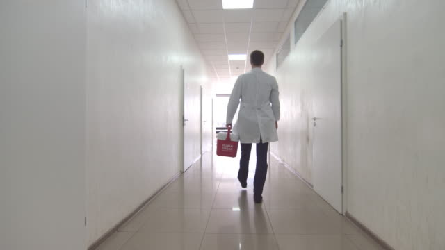 Doctor goes with red organ trafficking container at the clinic video