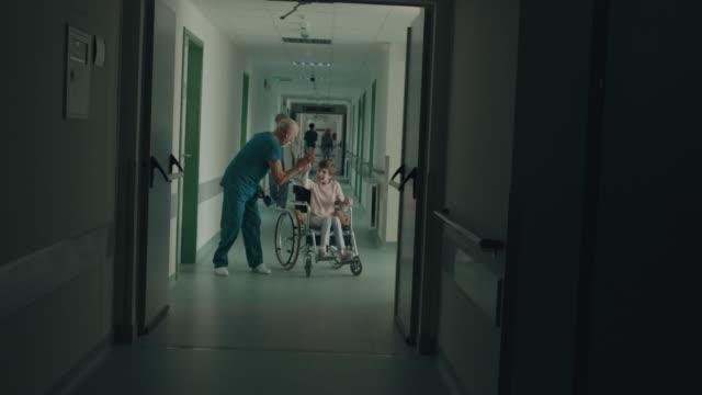 yüksek beşli tekerlekli sandalyede doktor tebrik kız - cerrahi önlük stok videoları ve detay görüntü çekimi