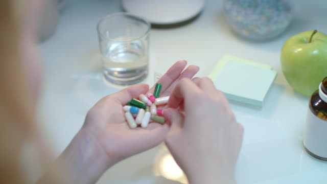 Doctor hand taking pills in pill dispenser. Woman sort drugs in organizer