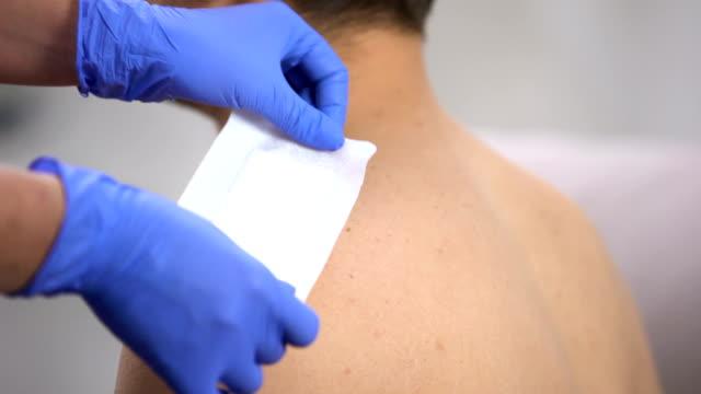 ręce lekarza stosujące bandaż samoprzylepny na porysowanym ramieniu męskiego pacjenta - rana filmów i materiałów b-roll