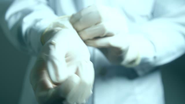 vídeos y material grabado en eventos de stock de manos de doctor con guantes de protección - guante quirúrgico