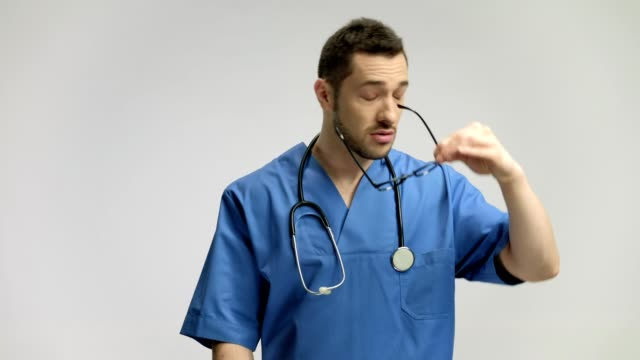 Doctor having a headache and massaging his forehead video