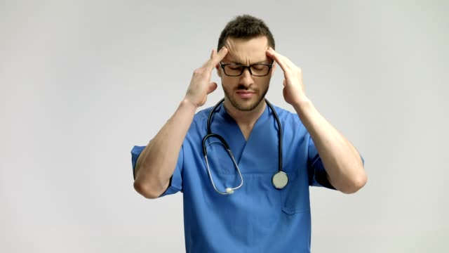 Doctor having a headache and massaging his temples video