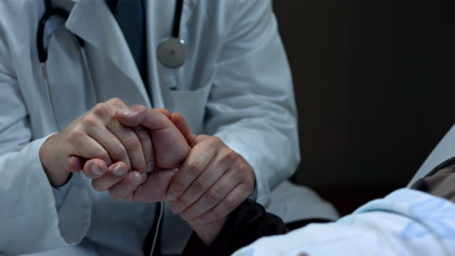 HD: Doctor Helping Patient Facing Death And Dying HD1080p: CLOSE-UP shot of a male doctor holding patient's hand while giving him a compassion and support facing death and dying. cancer patient stock videos & royalty-free footage