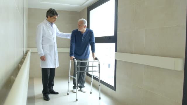 läkare hjälper ledande mannen i använder rörlighet walker - senior walking bildbanksvideor och videomaterial från bakom kulisserna