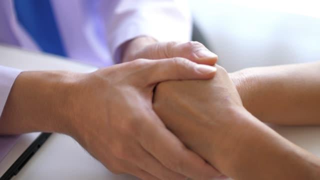 läkare höll patientens händer för uppmuntran, slowmotion - hålla handen bildbanksvideor och videomaterial från bakom kulisserna
