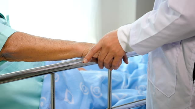 vídeos de stock e filmes b-roll de doctor holding senior patient's hands in bed at hospital room, health care and people concept - alzheimer