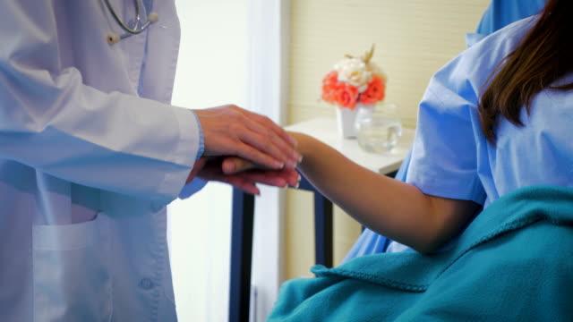 医師は病室、医療、人々 の概念でベッドで女性患者の手をつないで - 聴診器点の映像素材/bロール
