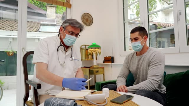Doctor in a home visit to a young man Doctor is talking with young man during home visit and writing his symptoms. general practitioner stock videos & royalty-free footage