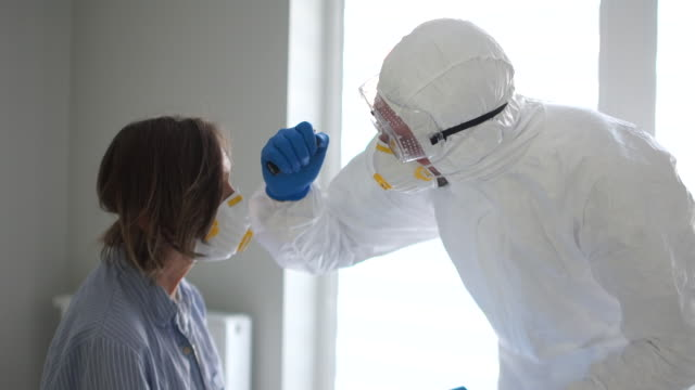 doctor in a protective mask and glasses examines a woman with a flashlight. pandemic threat, coronasirus threat - covid ospedale video stock e b–roll