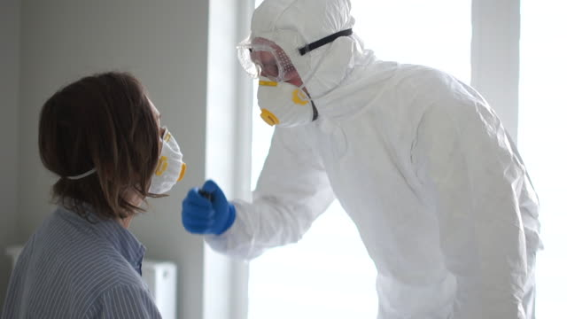 doctor in a protective suit examines a patient with a coronavirus. shines a flashlight in his mouth. coronavirus epidemic, the spread of dangerous influenza virus - covid ospedale video stock e b–roll