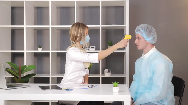 doctor in a white coat and a medical mask measures the temperature of a patient in the medical office with an infrared non-contact thermometer. - hand on glass covid video stock e b–roll