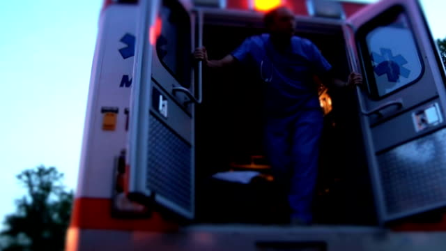 Doctor In Ambulance Doctor getting in ambulance. stretcher stock videos & royalty-free footage
