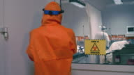 istock Doctor in an Orange Protective Suit Enters Isolation Room with Coronavirus Patients - Handheld Medium Tracking Shot 1210730053