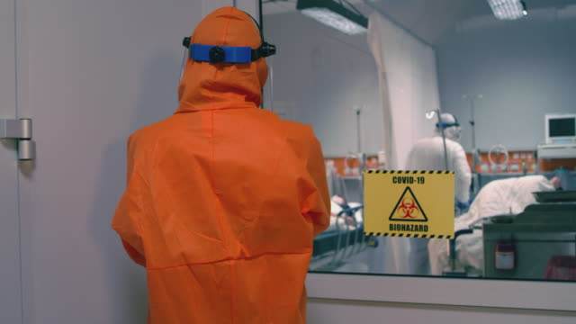 doctor in an orange protective suit enters isolation room with coronavirus patients - handheld medium tracking shot - odzież ochronna filmów i materiałów b-roll