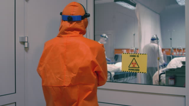 doctor in an orange protective suit enters isolation room with coronavirus patients - handheld medium tracking shot - covid ospedale video stock e b–roll