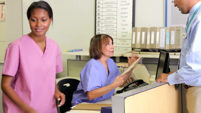 Médico y enfermera en debate en estación de enfermeras - vídeo