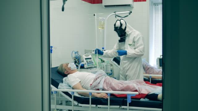 läkare i hazmat behandlar en person med coronavirus på sjukhus. coronavirus, covid-19 patient på intensivvårdsavdelning på ett sjukhus. - intensivvårdsavdelning bildbanksvideor och videomaterial från bakom kulisserna