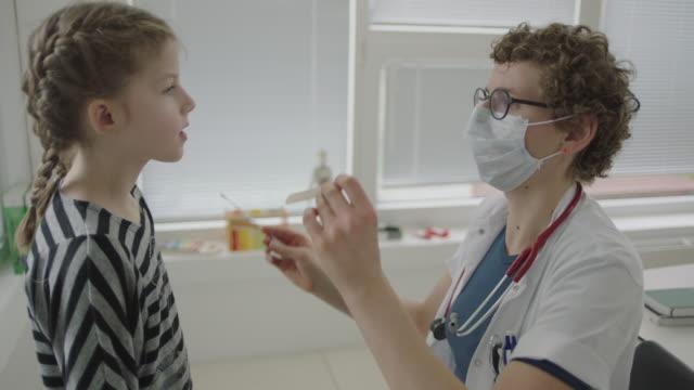 vidéos et rushes de docteur dans le masque utilisant l'écouvillon stérile pour tester pour le coronavirus sur la fille - enfant masque
