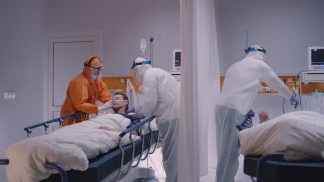 doctor in protective suit putting on oxygen mask on patient suffering from coronavirus - wide dolly shot - covid ospedale video stock e b–roll