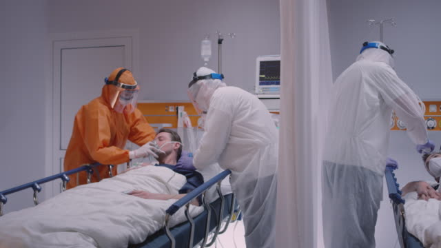 Video Doctor in Protective Suit Putting on Oxygen Mask on Patient Suffering from Coronavirus - Wide Dolly Shot
